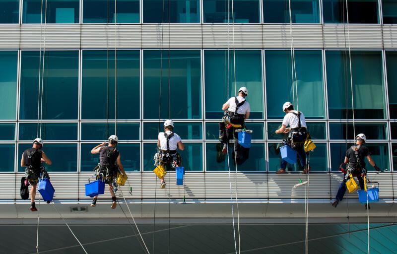 Team von kletternden Arbeitern auf Bürohaus Fassade